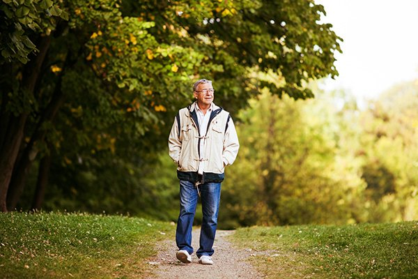 man walking alone on a nature path